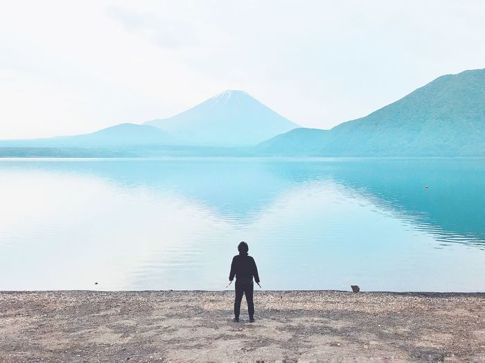 Rear view of man looking at lake against sky