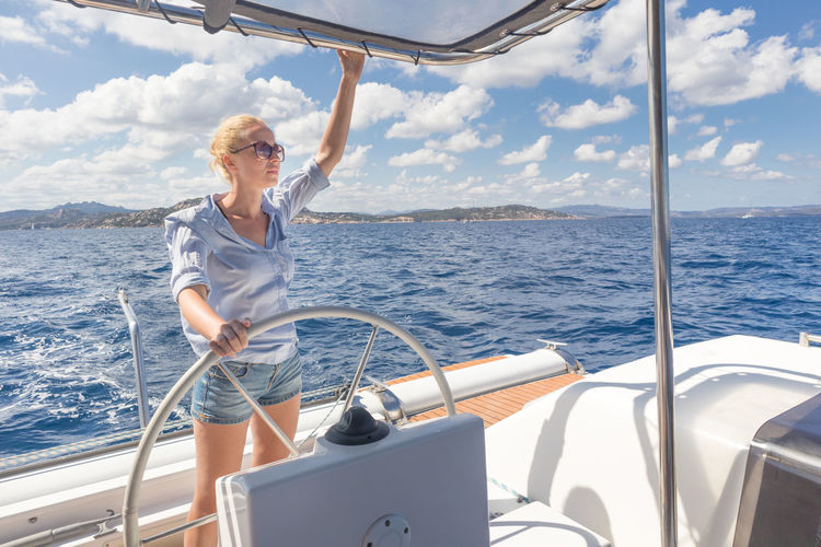 Woman looking away while standing on boat deck in sea against sky