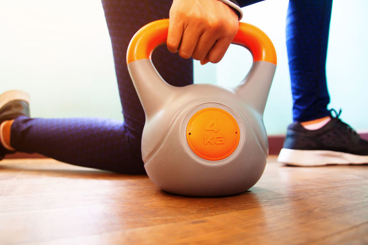 Woman's hand holding kettlebell, Home workout, Woman's health Exercising Home Slim Beauty Body Building Body Part Calories Close Up Equipment Fitness Gym Hand Human Body Part Human Hand Human Leg Kettlebell  Lifestyles Low Section Real People Sport Women Wood - Material Workout