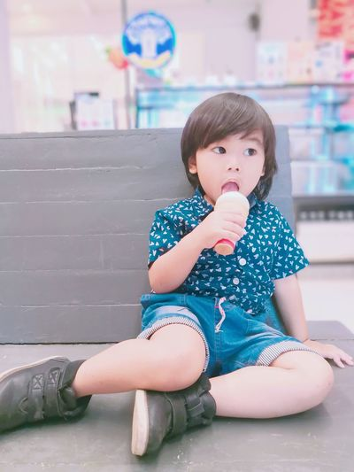 Thoughtful boy eating ice cream cone while sitting on bench