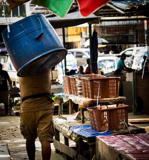 Rear view of man carrying container while walking in market