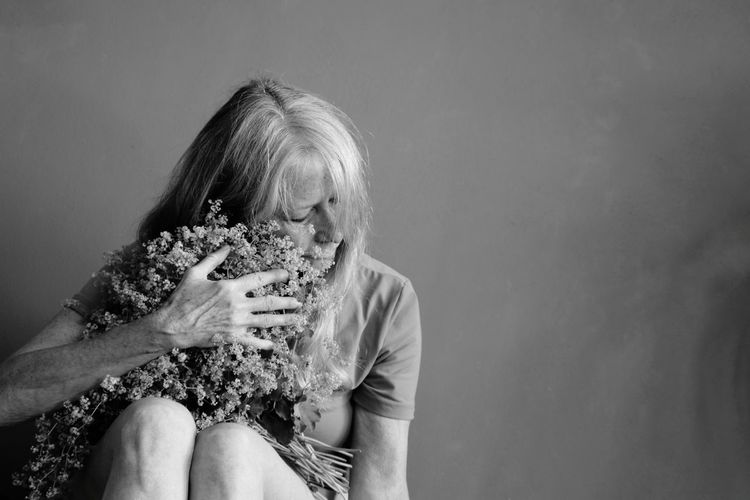 Sad woman holding flowering plant on gray background