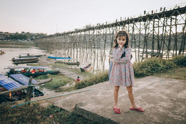 Full length portrait of girl standing against sky