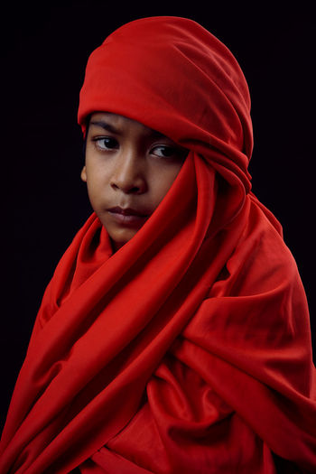 Portrait of boy wearing red textile against black background