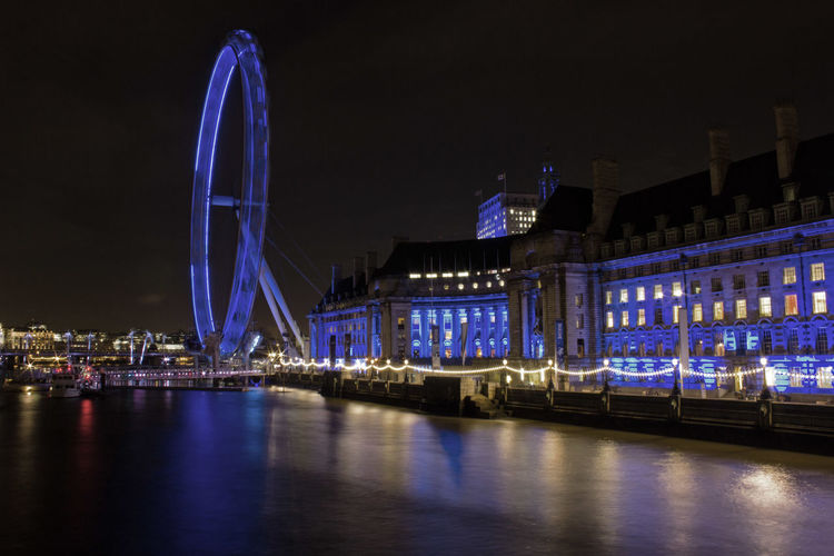 Illuminated London Eye By Thames River Against Sky At Night