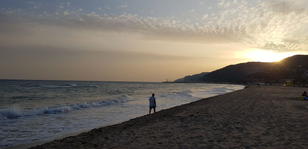 Rear view of man walking at beach against sky during sunset