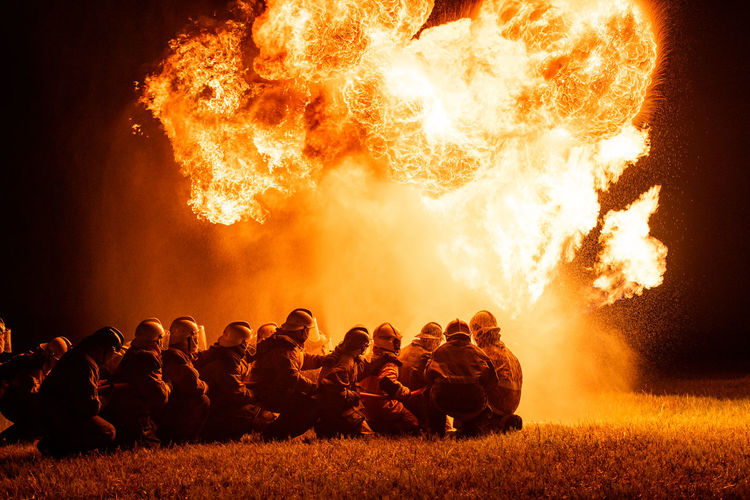 Firefighters crouching on land by fire at night
