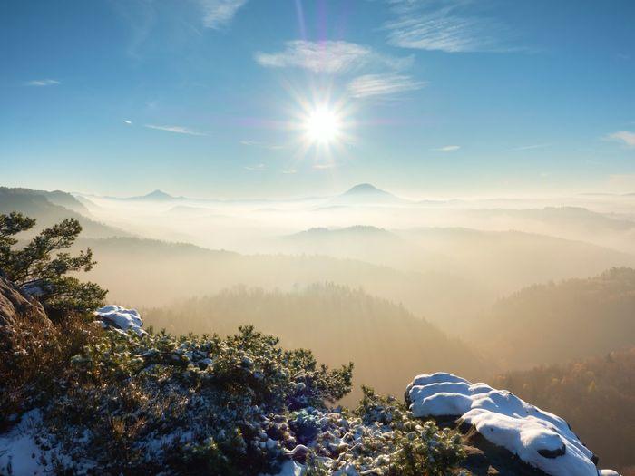 Freeze autumn trek, rocks covered with first fresh snow. stony peak, foggy valley. winter misty day