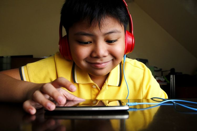 Close-up of boy listening to headphones while using smart phone