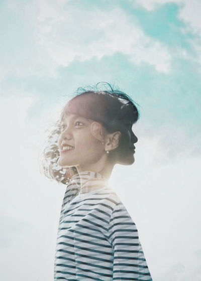 Double exposure of smiling woman against cloudy sky