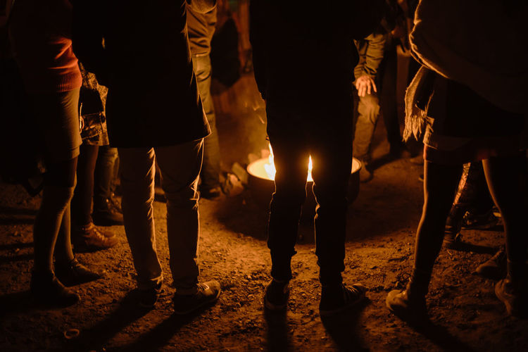 Low section of people standing by bonfire at night