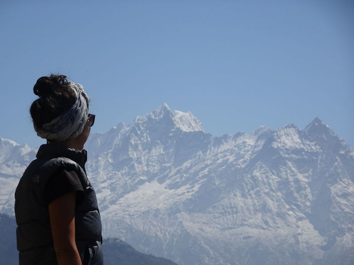 Woman looking at snowcapped mountain against clear sky
