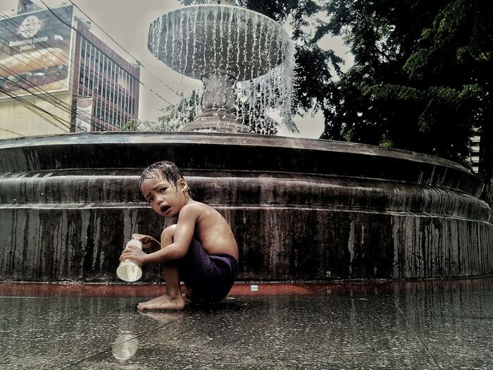 Portrait of boy sitting by fountain