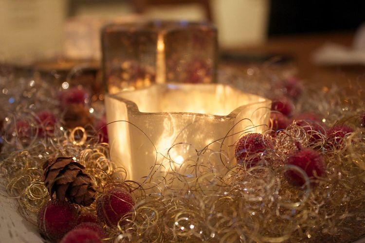 Close-up of illuminated candle amidst christmas decoration
