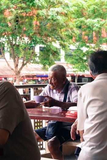 Senior Man Having Food At Sidewalk Cafe