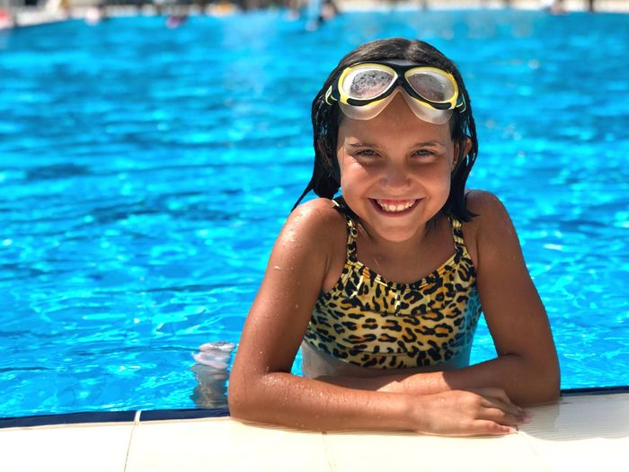 Portrait of smiling girl in swimming pool on sunny day