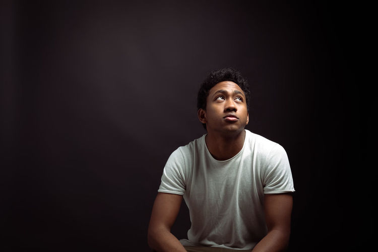 Portrait of young man looking away against black background