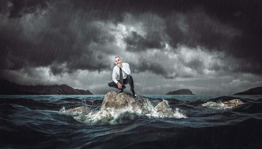 Digital composite image of man standing in sea against sky