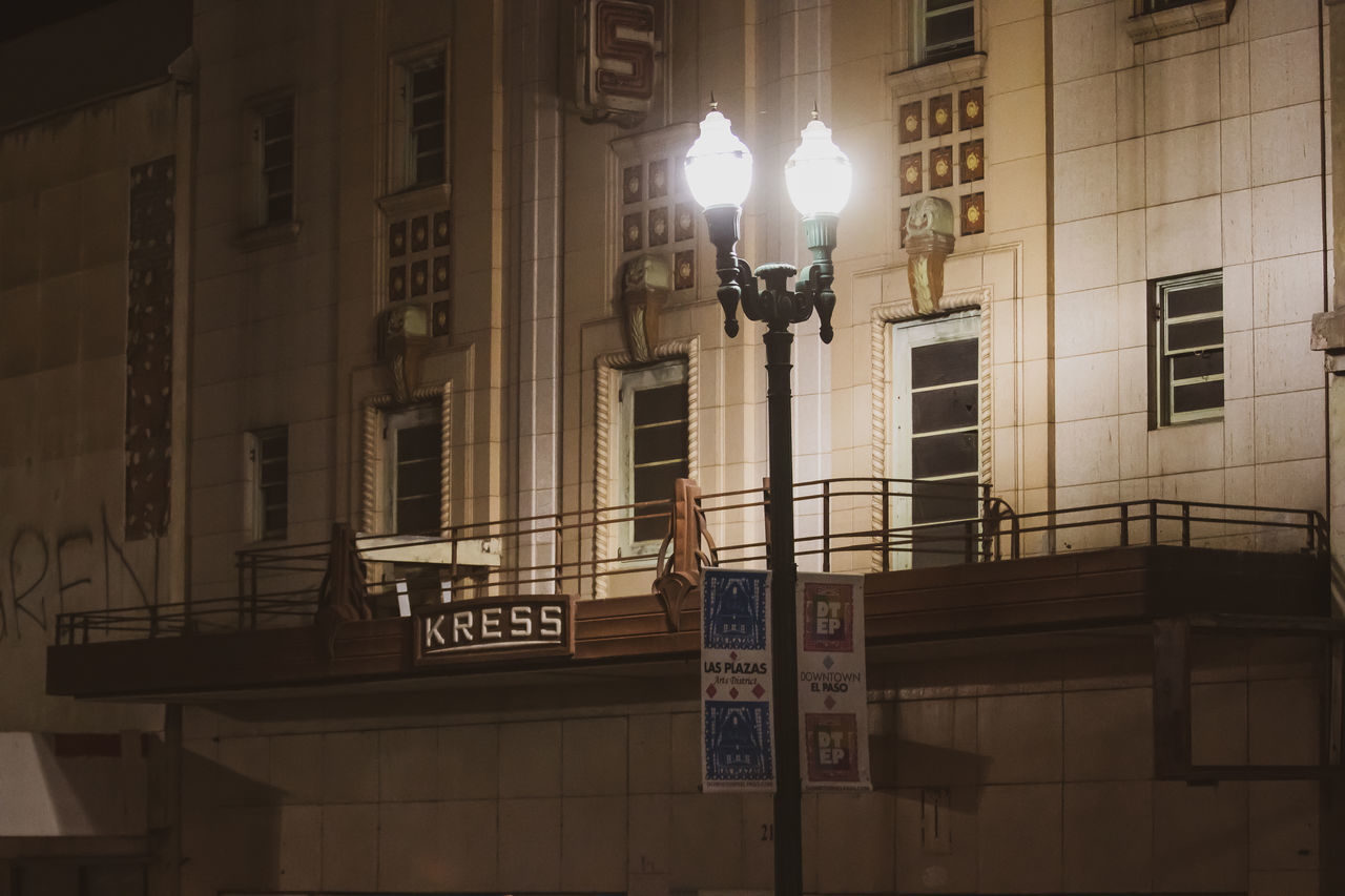 built structure, illuminated, architecture, lighting equipment, building exterior, building, street light, street, text, communication, low angle view, city, western script, night, window, wall - building feature, outdoors, sign, railing, one person, electric lamp