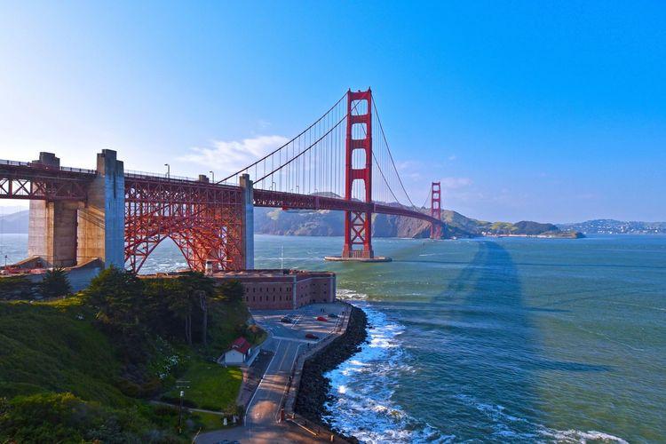 Golden gate bridge over river against blue sky