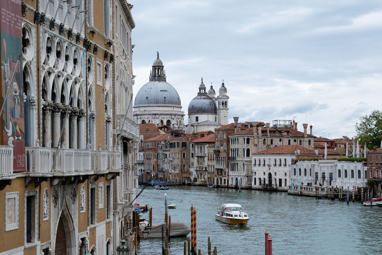 Boats in canal by buildings in venice against sky