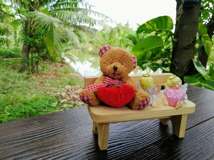 Stuffed toy on table against trees