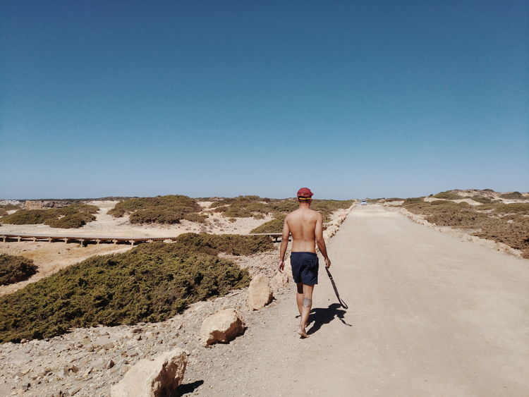 One Person Rear View Full Length Sand Sunny Day One Man Only People Clear Sky Adult Adults Only Sky Shirtless Outdoors Dog Beach Only Men Sand Dune Sand Pail And Shovel Travel Destinations Peaceful