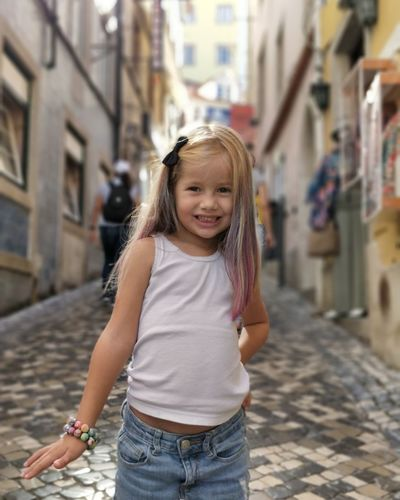 Portrait of smiling girl standing on footpath
