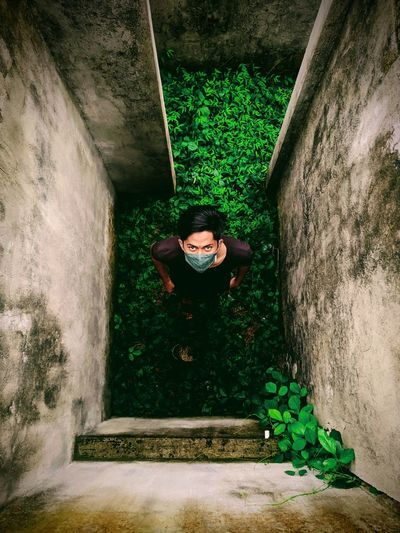 High angle portrait of man wearing mask standing on green land amidst wall
