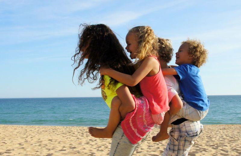 Side View Of Siblings Enjoying At Beach Against Sky