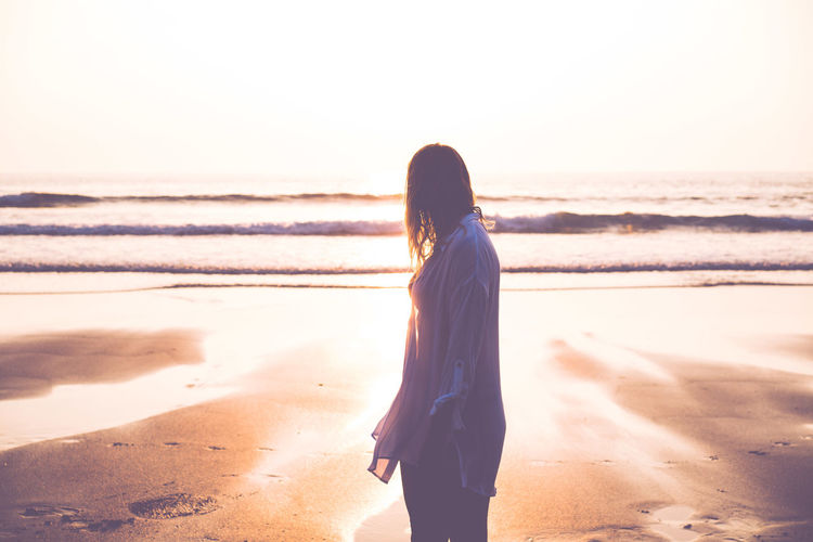 Side view of woman standing at beach during sunset