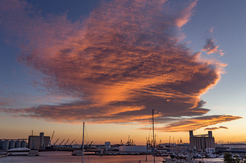Sailboats on harbor against sky during sunset