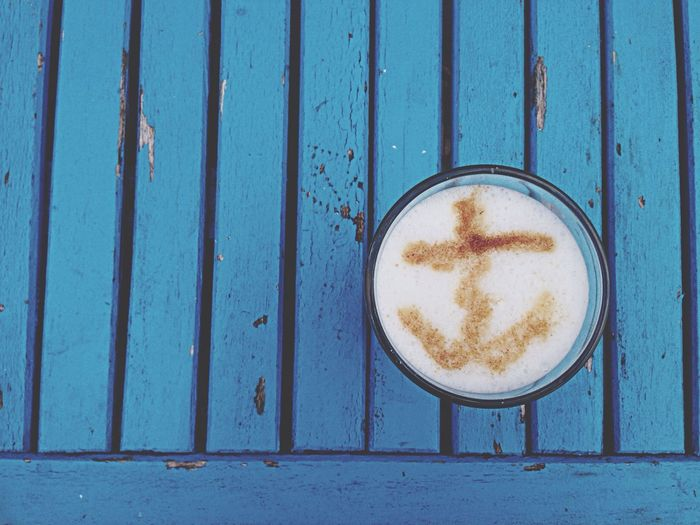 Latte art in glass of coffee on blue wooden table