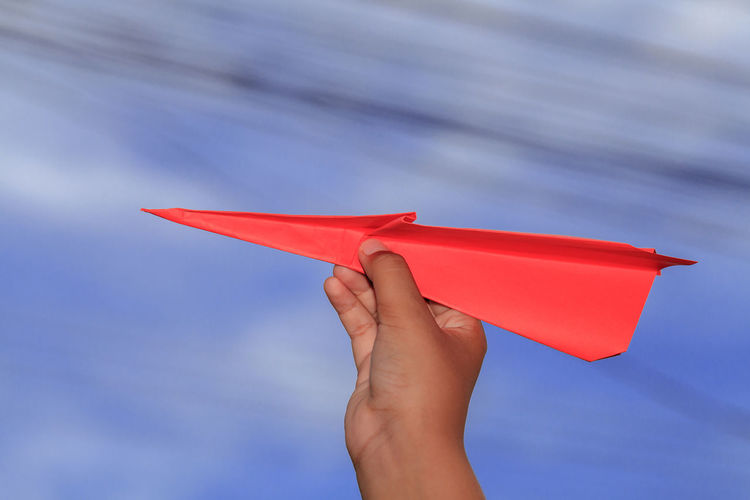 Air Vehicle Airplane Childhood Close-up Cloud - Sky Day Finger Hand Holding Human Body Part Human Hand Low Angle View Nature One Person Orange Color Paper Paper Airplane Personal Perspective Red Sky Toy
