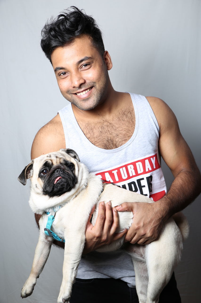 one person, casual clothing, dog, pets, happiness, front view, holding, smiling, studio shot, indoors, real people, young adult, portrait, looking at camera, lifestyles, gray background, men, day, people