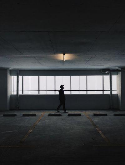 Side view of silhouette man walking in corridor