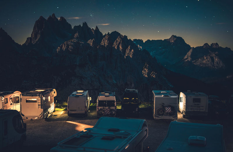 Panoramic view of illuminated mountains against sky at night