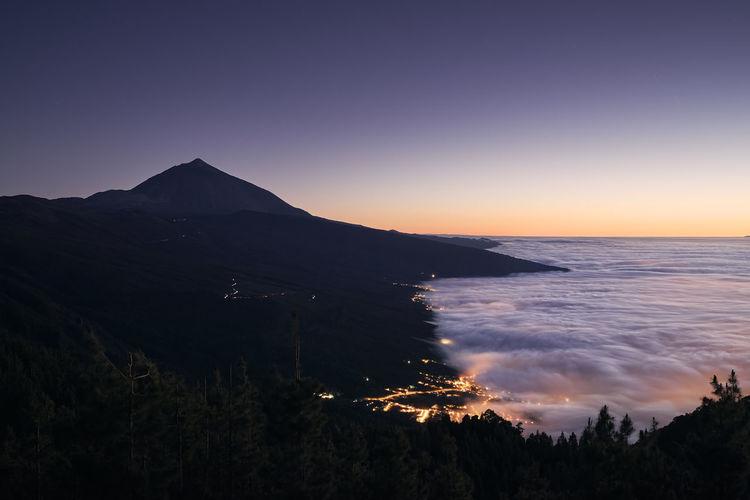 Landscape with volcano pico de teide above clouds at beautiful dusk.