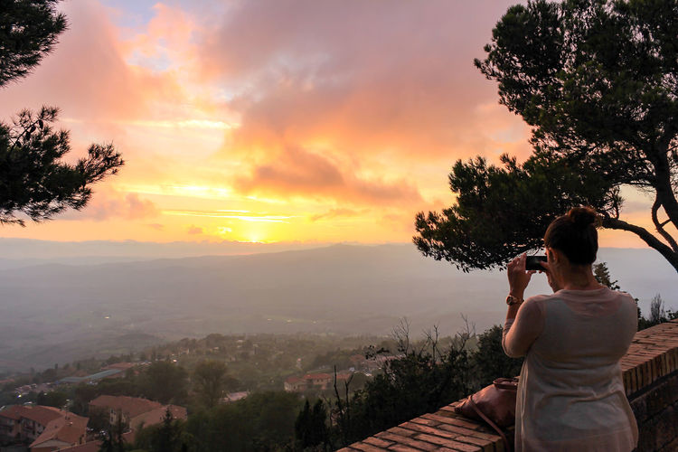 Woman photographing mountains against sky during sunset