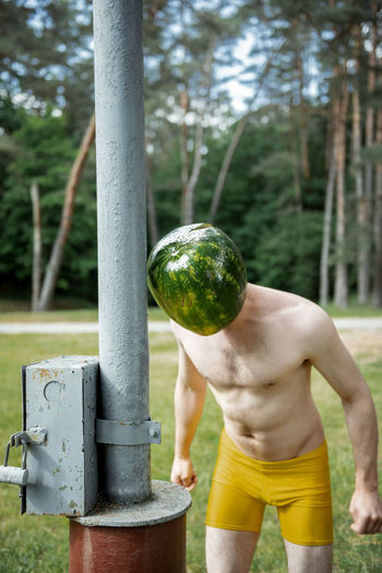 Shirtless man wearing face covered with watermelon on land