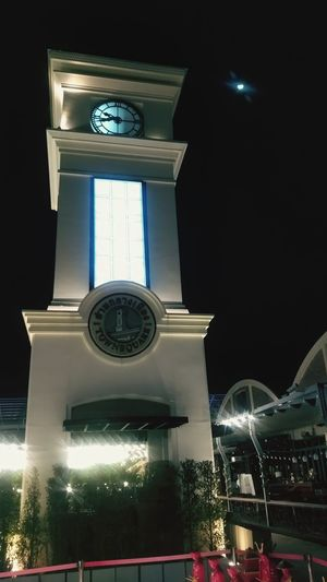 Low angle view of illuminated clock tower at night