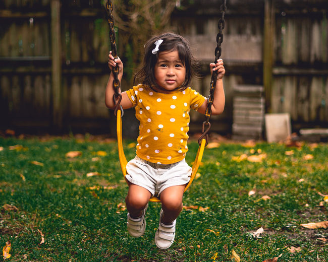 Portrait of cute girl on swing in playground
