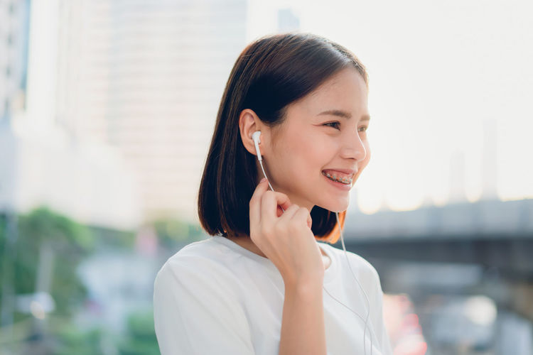 Women are listening to music from white headphones. And using hands touch to use various functions, happy mood. One Person Focus On Foreground Happiness Young Adult Headshot Smiling Women Young Women Emotion Architecture Portrait Looking Built Structure Adult Looking Away Lifestyles Beautiful Woman Real People Using Phone Hairstyle Outdoors