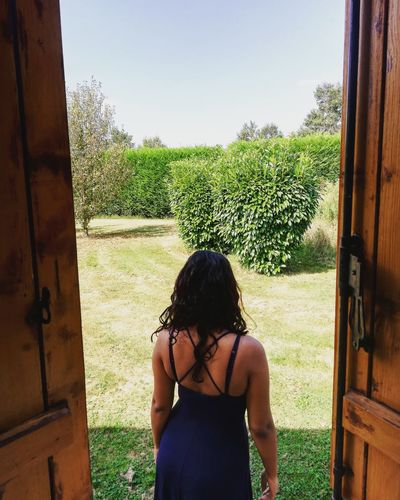 Rear view of woman standing by open door against sky