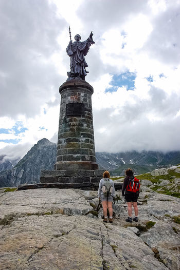 Hikers standing on monument at great st bernard pass