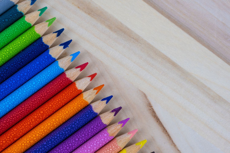 High angle view of multi colored pencils on wood