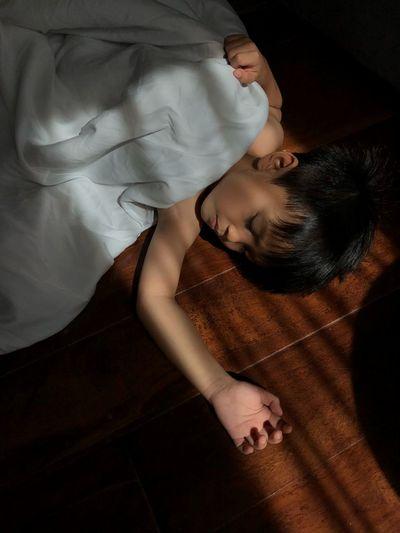 High angle view of boy sleeping on floorboard