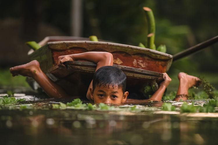 Portrait of cute boy in water