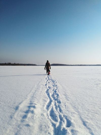 Full length of woman with dog walking on snowy field against clear sky