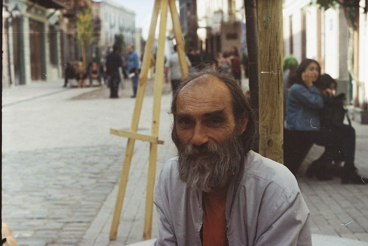 Portrait of homeless man sitting at city street